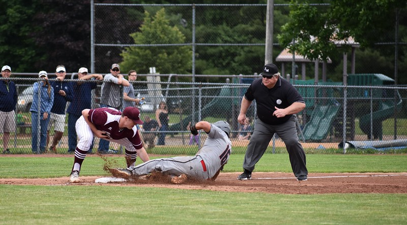 "Orono third baseman Connor Robertson applies the tag to Lisbon's Lucas Francis on an attempted steal during the sixth inning of Saturday's Class C baseball state championship game at Mansfield Stadium in Bangor. Umpire Chris Parker prepares to make the ""out"" call. Orono won 4-3."