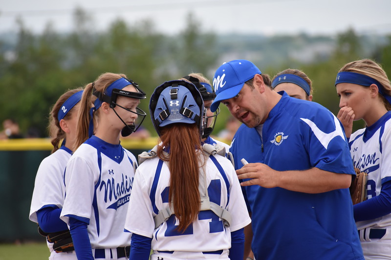 Madison softball coach Chris LeBlanc talks with team members during a visit to the pitcher's circle in Saturday's Class C softball state championship game against Madison at Coffin Field in Brewer.