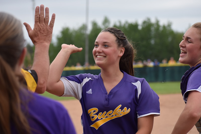 Katelin Saunders of Bucksport High School receives high-fives from her coach and teammates after finishing off an inning during Saturday's Class C softball state title game against Madison at Coffin Field in Brewer. Saunders pitched the Golden Bucks to a 2-1 victory.