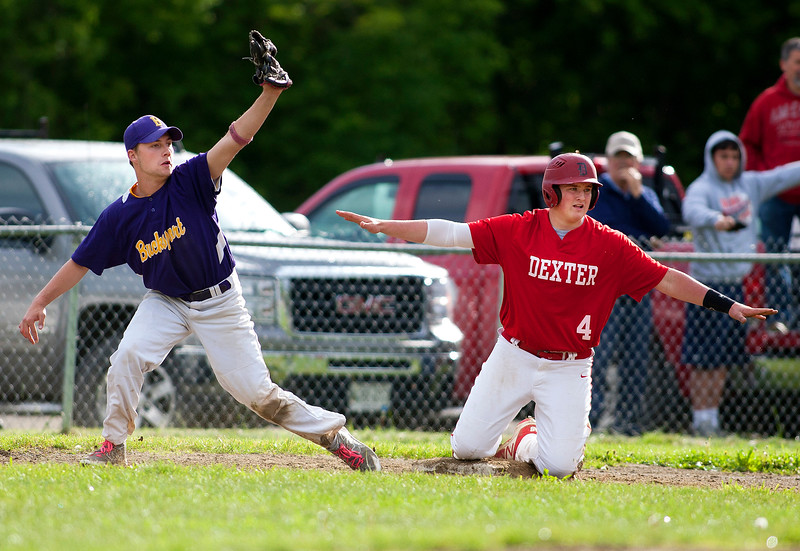 DEXTER, Maine -- 06/02/2017 - Dexter's Brayden Miller (right) makes the safe sign after sliding into third past Bucksport's Matt Vincent during their baseball game in Dexter Friday. Ashley L. Conti | BDN