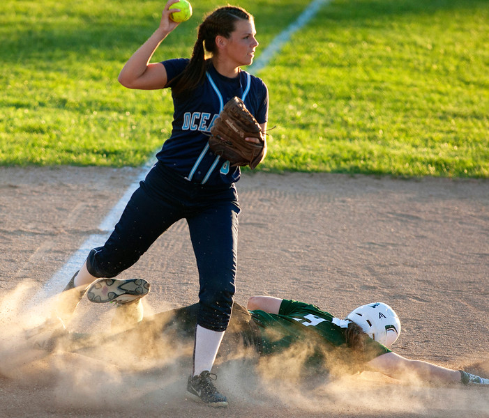 BREWER, Maine -- 06/13/2017 - Oceanside's Casey Pine (left) looks to throw to first after getting Old Town's Hannah Sibley out at third during their Class B North softball championship game at Coffin Field in Brewer Tuesday. Ashley L. Conti | BDN