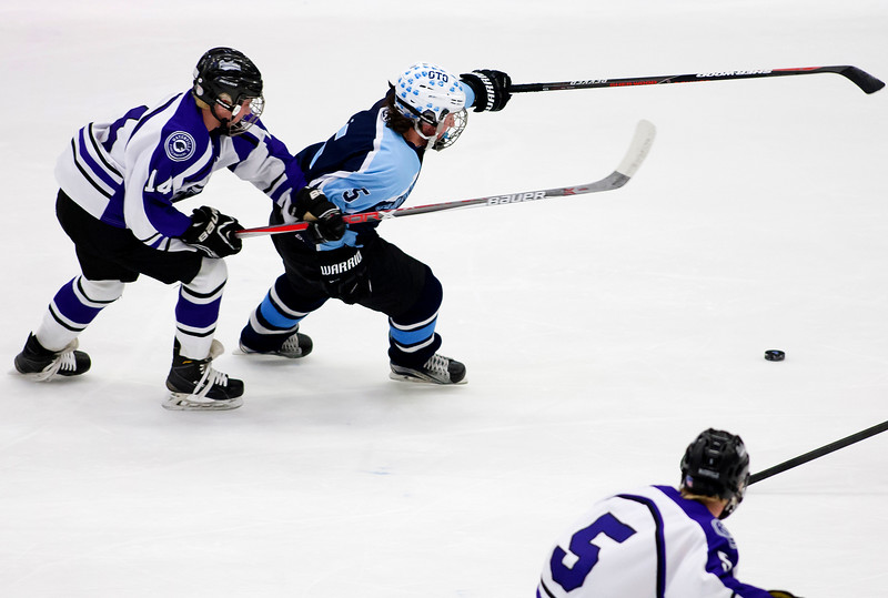 ORONO, Maine -- 03/07/2017 -- Old Town-Orono's Tyler Wheeler (right) and Waterville's Michael Bolduc battle for the puck during their Class B North hockey championship game at Alfond Arena in Orono Tuesday. Ashley L. Conti | BDN