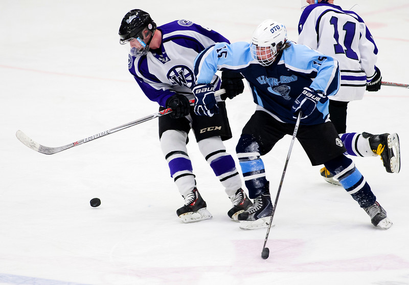 ORONO, Maine -- 03/07/2017 -- Waterville's Justin Wentworth (left) tries to regain control of the puck against Old Town-Orono's Sam Henderson during their Class B North hockey championship game at Alfond Arena in Orono Tuesday. Ashley L. Conti | BDN
