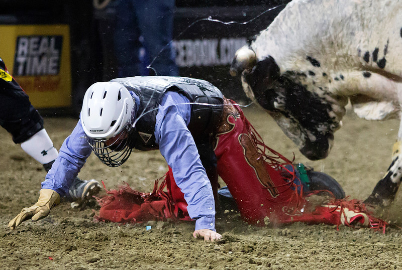 """BANGOR, Maine -- 03/11/2017 -- Quentin Vaught tries to escape from Smokin Do Dad during the Professional Bull Riders Velocity Tour """"Bangor Buck Off,"""" at Cross Insurance Center in Bangor Saturday. Ashley L. Conti 