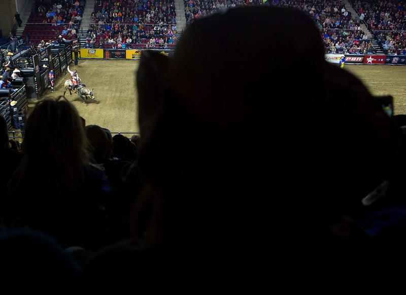 "BANGOR, Maine -- 03/11/2017 -- Fans watch as a rider tries to stay on a bull during the Professional Bull Riders Velocity Tour ""Bangor Buck Off,"" at Cross Insurance Center in Bangor Saturday. Ashley L. Conti 
