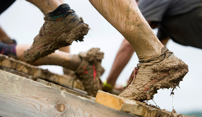 ORRINGTON, Maine -- 07/01/2017 - Muddy shoes of a racer navigate an obstacle during the inaugural Wicked Muddy Mainer obstacle course race at the Thornton Family Campground in Orrington Saturday. More than 700 racers made their way through four miles filled with mud, hills, water, and 14 obstacles.  Ashley L. Conti | BDN