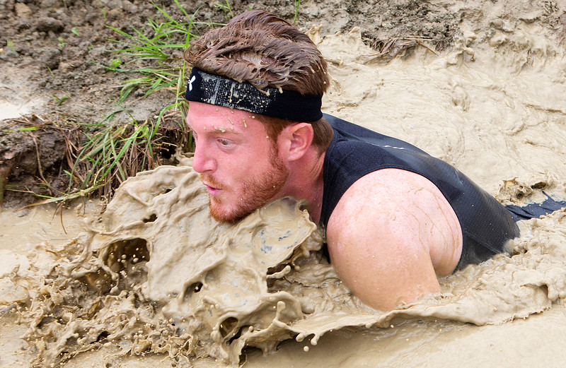 ORRINGTON, Maine -- 07/01/2017 - A racer emerges from a muddy trench during the inaugural Wicked Muddy Mainer obstacle course race at the Thornton Family Campground in Orrington Saturday. More than 700 racers made their way through four miles filled with mud, hills, water, and 14 obstacles.  Ashley L. Conti | BDN