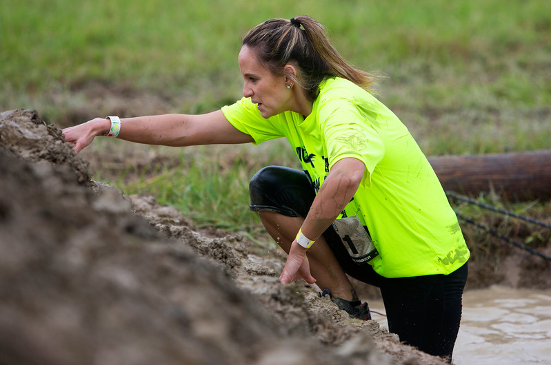 ORRINGTON, Maine -- 07/01/2017 - Jamie Kingston<br /> makes her way up a muddy hill during the inaugural Wicked Muddy Mainer obstacle course race at the Thornton Family Campground in Orrington Saturday. More than 700 racers made their way through four miles filled with mud, hills, water, and 14 obstacles.  Ashley L. Conti | BDN