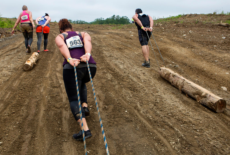 ORRINGTON, Maine -- 07/01/2017 - Racers pull logs up a hill during the inaugural Wicked Muddy Mainer obstacle course race at the Thornton Family Campground in Orrington Saturday. More than 700 racers made their way through four miles filled with mud, hills, water, and 14 obstacles.  Ashley L. Conti | BDN
