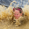 ORRINGTON, Maine -- 07/01/2017 - A racer slashes into water after taking a trip on a giant slide during the inaugural Wicked Muddy Mainer obstacle course race at the Thornton Family Campground in Orrington Saturday. More than 700 racers made their way through four miles filled with mud, hills, water, and 14 obstacles.  Ashley L. Conti | BDN