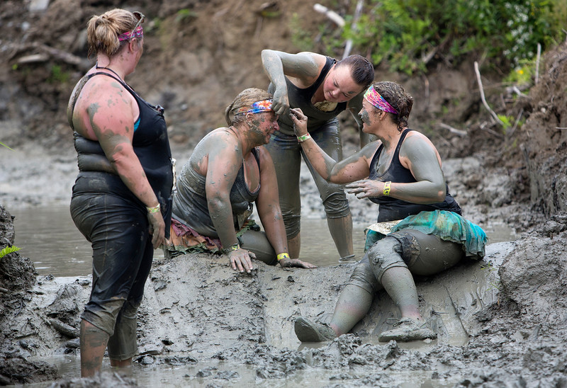 ORRINGTON, Maine -- 07/01/2017 - Olivia Galland (center), 16, and Denise Crandall (right) help get mud out of the eye of Jamie McNeil while Ginger Allen watches during the inaugural Wicked Muddy Mainer obstacle course race at the Thornton Family Campground in Orrington Saturday. More than 700 racers made their way through four miles filled with mud, hills, water, and 14 obstacles.  Ashley L. Conti | BDN