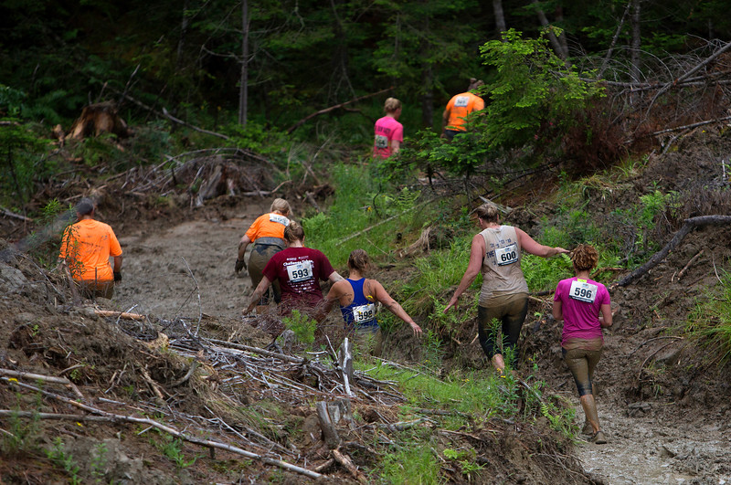 ORRINGTON, Maine -- 07/01/2017 - Racers navigate a muddy path during the inaugural Wicked Muddy Mainer obstacle course race at the Thornton Family Campground in Orrington Saturday. More than 700 racers made their way through four miles filled with mud, hills, water, and 14 obstacles.  Ashley L. Conti | BDN