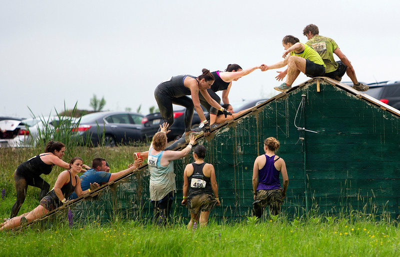 ORRINGTON, Maine -- 07/01/2017 - Racers help each other over an obstacle during the inaugural Wicked Muddy Mainer obstacle course race at the Thornton Family Campground in Orrington Saturday. More than 700 racers made their way through four miles filled with mud, hills, water, and 14 obstacles.  Ashley L. Conti   BDN