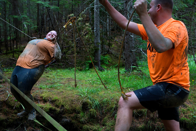 ORRINGTON, Maine -- 07/01/2017 - Nicole Pomeroy (left) tries to keep her balance while Cody Harriman tries to steady the line on a slack line obstacle during the inaugural Wicked Muddy Mainer obstacle course race at the Thornton Family Campground in Orrington Saturday. More than 700 racers made their way through four miles filled with mud, hills, water, and 14 obstacles.  Ashley L. Conti | BDN