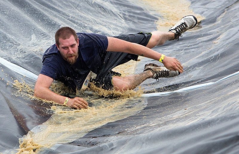 ORRINGTON, Maine -- 07/01/2017 - Mat Winchester makes his way down a slide during the inaugural Wicked Muddy Mainer obstacle course race at the Thornton Family Campground in Orrington Saturday. More than 700 racers made their way through four miles filled with mud, hills, water, and 14 obstacles.  Ashley L. Conti | BDN