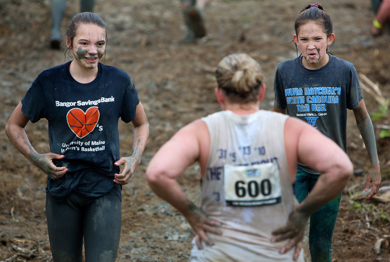 ORRINGTON, Maine -- 07/01/2017 - Muddy faced racers make their way through course during the inaugural Wicked Muddy Mainer obstacle course race at the Thornton Family Campground in Orrington Saturday. More than 700 racers made their way through four miles filled with mud, hills, water, and 14 obstacles.  Ashley L. Conti | BDN