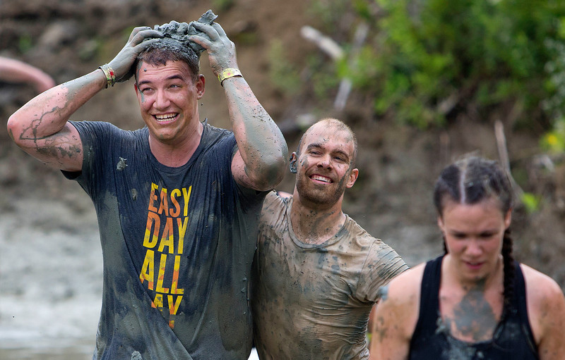 ORRINGTON, Maine -- 07/01/2017 - Luke Edwards (center) puts mud on Daniel Wendell during the inaugural Wicked Muddy Mainer obstacle course race at the Thornton Family Campground in Orrington Saturday. More than 700 racers made their way through four miles filled with mud, hills, water, and 14 obstacles.  Ashley L. Conti | BDN