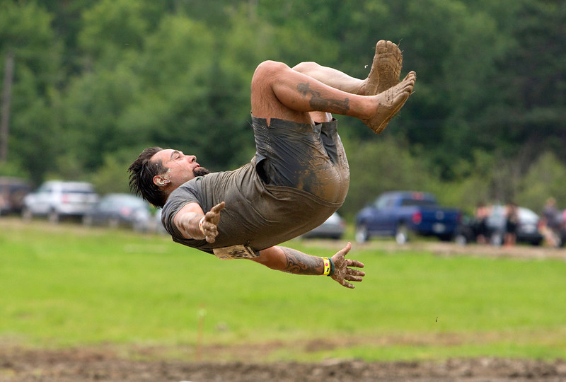 ORRINGTON, Maine -- 07/01/2017 - A racer does a backflip into water during the inaugural Wicked Muddy Mainer obstacle course race at the Thornton Family Campground in Orrington Saturday. More than 700 racers made their way through four miles filled with mud, hills, water, and 14 obstacles.  Ashley L. Conti | BDN