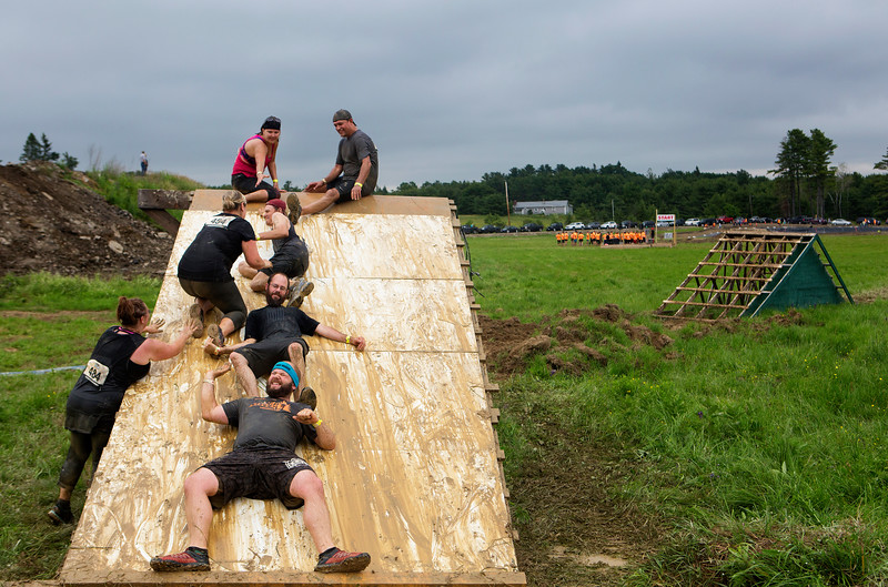 ORRINGTON, Maine -- 07/01/2017 - Racers work together to navigate an obstacle during the inaugural Wicked Muddy Mainer obstacle course race at the Thornton Family Campground in Orrington Saturday. More than 700 racers made their way through four miles filled with mud, hills, water, and 14 obstacles.  Ashley L. Conti | BDN