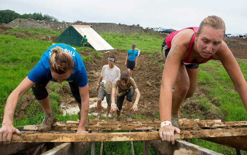 ORRINGTON, Maine -- 07/01/2017 - Racers climb up an obstacle during the inaugural Wicked Muddy Mainer obstacle course race at the Thornton Family Campground in Orrington Saturday. More than 700 racers made their way through four miles filled with mud, hills, water, and 14 obstacles.  Ashley L. Conti | BDN