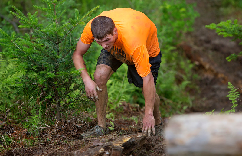 ORRINGTON, Maine -- 07/01/2017 - A racer makes his way to the top of a hill during the inaugural Wicked Muddy Mainer obstacle course race at the Thornton Family Campground in Orrington Saturday. More than 700 racers made their way through four miles filled with mud, hills, water, and 14 obstacles.  Ashley L. Conti | BDN