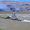 Barge and tug entering main stream of Snake River below Lower Monumental Dam,. June 12, 2010