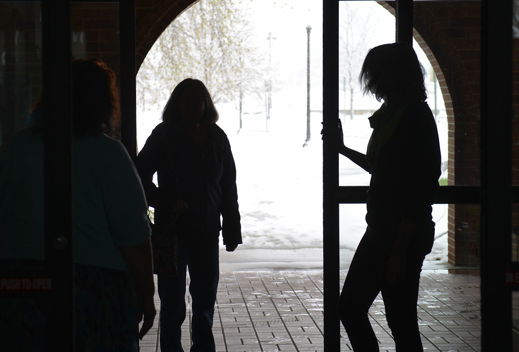 Justin Sheely | The Sheridan Press<br /> Library staff open the sliding doors for a visitor during a power outage Tuesday morning at the Sheridan County Fulmer Public Library. Much of downtown Sheridan was without power for about an hour during Tuesday's spring snow. Many parts of the county experienced outages throughout the day.