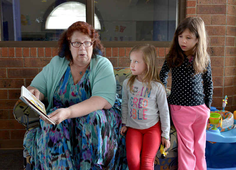 Justin Sheely | The Sheridan Press<br /> Children's Librarian Michelle Havenga reads a book at Kelly Tuttle and Amelia Martin, 5, during a power outage Tuesday morning at the Sheridan County Fulmer Public Library. Much of downtown Sheridan was without power for about an hour during Tuesday's spring snow. Many parts of the county experienced outages throughout the day.