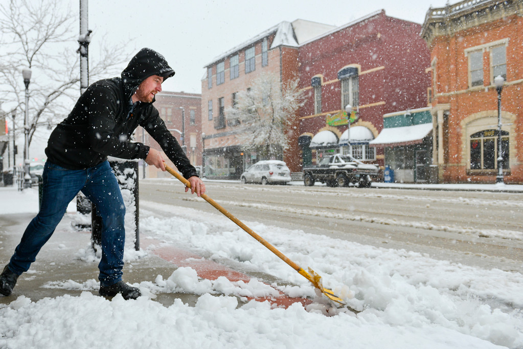 Justin Sheely | The Sheridan Press<br /> Jeff Garrelts, co-owner of the Cottonwood Shop, removes slushy snow from the sidewalk Tuesday morning on Sheridan's Main Street. The National Weather Service predicts 3-6 inches of heavy snow in the area.
