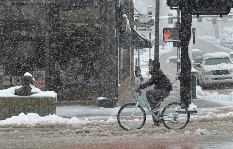 Justin Sheely | The Sheridan Press<br /> A bicyclist rides through the slush Tuesday morning along Sheridan's Main Street. Much of downtown Sheridan was without power for about an hour during Tuesday's spring snow. Many parts of the county experienced outages throughout the day.