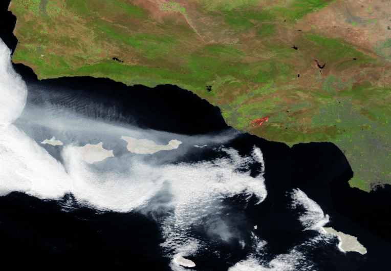 . This satellite photo released by NOAA, National Oceanic and Atmospheric Administration, showing a stream of smoke clearly visible moving west over the ocean, as are the heat signatures from the active fires areas.  A Southern California wildfire carving a path to the sea grew to more than 15 square miles and crews prepared Friday for another bad day of gusting winds and searing weather. (AP Photo/NOAA via NASA)