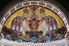 "St. Bridget's church, Apse painting<br /> <br /> APSE PAINTING The apse mural was commissioned along with the windows by Monsignor Aughney for the Golden Jubilee in 1937. Once again quoting from the 1951 School and Convent Dedication Book, the apse painting is described as follows:<br /> <br /> The mural pictures Jesus Christ, the King of Kings and Divine High Priest, offering Himself on the altar of the cross to His Heavenly Father. Wearing a royal crown and priestly robes, He is surrounded by a blaze of glory in unity with the other two Divine Persons of the Holy Trinity: God the Father, symbolized by a hand pointing to the Savior in token of the words, ""This is my Beloved Son in Whom I am well pleased""; and God the Holy Spirit in the form of a dove.<br /> <br /> On either side of the Savior in the Holy Eucharist are pictured angels bearing symbols of the other six sacraments of the Church, whose worth all comes from the Sacrifice of Christ on the cross and continued in the mass.<br /> <br /> THE FIRST ANGEL bears a font symbolic of the first and most necessary sacrament, Baptism.<br /> <br /> THE SECOND ANGEL carries the cross and the keys symbolic of Reconciliation. The cross is a sign of forgiveness and the keys symbolize the power ""to bind and to loose"" --""I will give to thee the keys of the kingdom of heaven.""<br /> <br /> THE THIRD ANGEL has on his shield the crosier, which signifies the Bishop's power to confirm his flock, thereby strengthening their faith through the Sacrament of Confirmation. The seven tongues of fire represent the gifts of the Holy Spirit, viz.: Wisdom, Understanding, Counsel, Fortitude, Knowledge, Piety and Fear of the Lord.<br /> <br /> THE FOURTH ANGEL on the other side of Christ, bears the symbol of Matrimony: the two hands joined under the priestly stole.<br /> <br /> THE FIFTH ANGEL with the chalice and missal on his shield represents the Sacrament of Holy Orders.<br /> <br /> THE SIXTH ANGEL bears the symbol representing the Sacrament of the Sick.<br /> <br /> Springing from the cross is the luxuriant vine symbolic of the Mystical Body of Christ, for He is the Vine of which we are the branches. The vine, bearing rich clusters of grapes, may be understood to mean the continuation of the Sacrifice of the Cross in the unbloody Sacrifice of the Mass under the appearance of bread an wine.<br /> <br /> The seven stained glass windows in the apse are described in the following photos. Only five of the windows are visible in most of the church."
