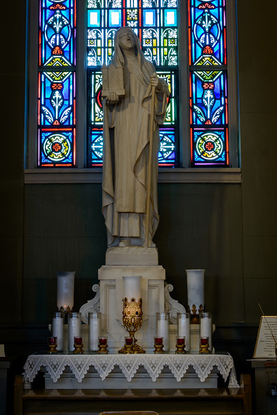 St. Bridget's church, Christ the Worker window, St. Bridget statue<br /> <br /> STATUE - ST. BRIDGET  The saint is holding a miniature church. Art historically, this symbolizes the patroness' intervention on behalf of the parish itself.