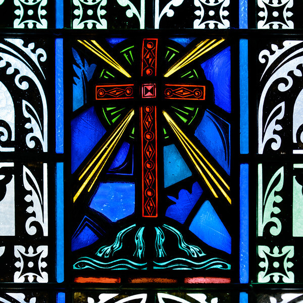 """Baptistry window. This window with the cross at the center represents the words of St. Paul from Romans 6:3: """"Are you unaware that we who were baptized into Christ Jesus were baptized into his death""""."""
