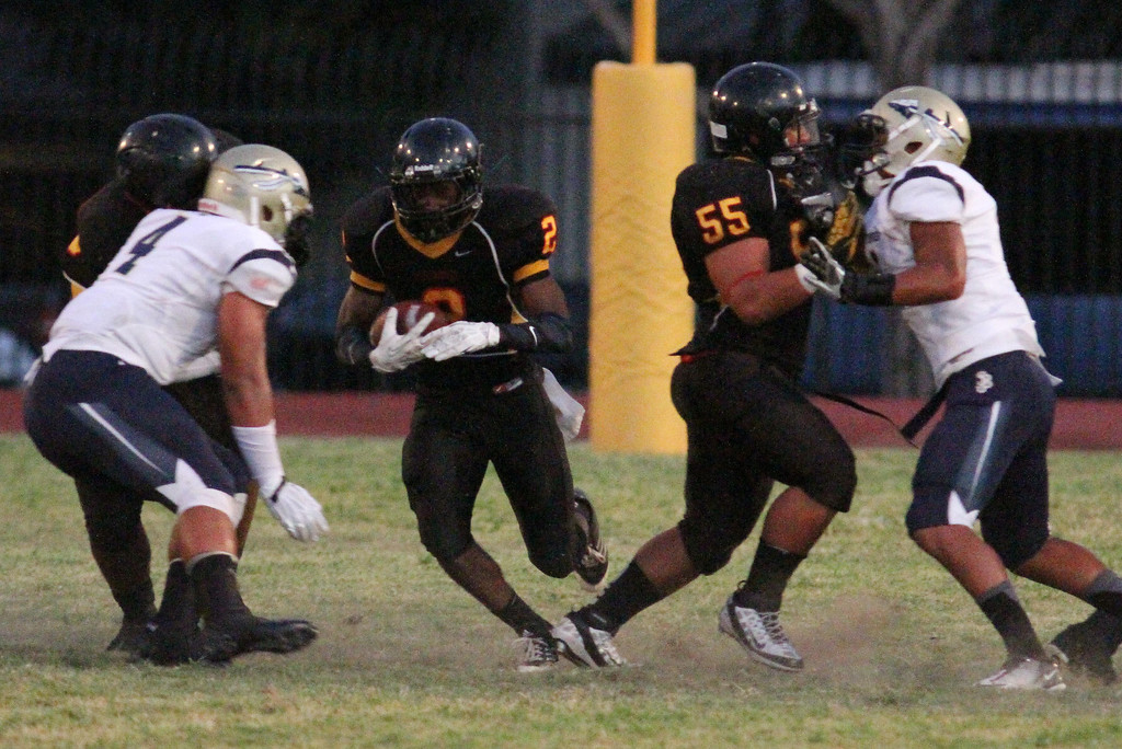 . August 30, 2013. Dominguez\'s Joshua Ford (2), center, breaks through a hole in the line to pick up some yardage during Friday nights game at Dominguez High School in Compton, California. (Mark Dustin/For the Long Beach Press-Telegram)