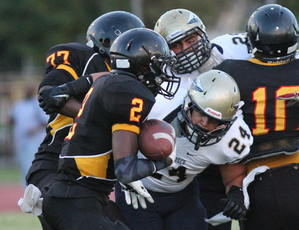 . August 30, 2013. Dominguez\'s Joshua Ford (2), left, looks to get by St. John Bosco\'s Jason Lucero (24), center, during Friday nights game at Dominguez High School in Compton, California. (Mark Dustin/For the Long Beach Press-Telegram)