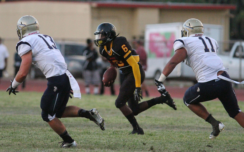. August 30, 2013. Dominguez\'s Aaron Fleming (6), center, tries to outrun St. John Bosco\'s Cole McNamara (13), left, and Jacob Tuioti-Mariner (11), right, during Friday nights game at Dominguez High School in Compton, California. (Mark Dustin/For the Long Beach Press-Telegram)