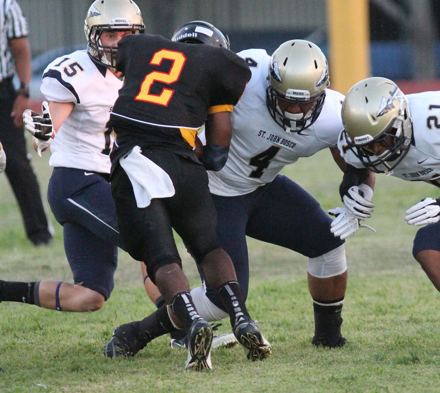 . August 30, 2013. St. John Bosco\'s Brett Baldwin (15), Chandler Leniu (4), and Chandler Hawkins (21), left to right, converge on Dominguez\'s Joshua Ford (2), center, during Friday nights game at Dominguez High School in Compton, California. (Mark Dustin/For the Long Beach Press-Telegram)