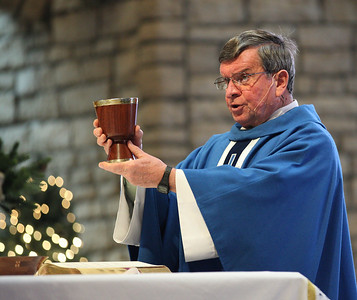 Fr. Frank Kosem changes the wine into the blood of Jesus during New year's Day Mass at St. Jude's Church.    photo by Ray Riedel