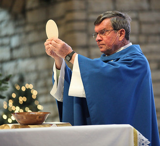 Fr. Frank Kosem changes the bread into the body of Jesus during New year's Day Mass at St. Jude's Church.   photo by Ray Riedel