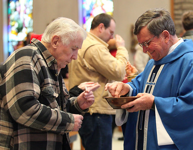 Dick Brent receives Holy Communion from Father Kosem at St. Jude's on New Years Day, a day of obligation for Catholics.   photo by Ray Riedel