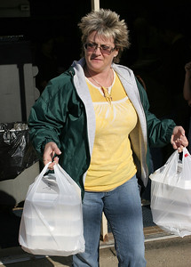 Deb LaVigne carries a batch of thanksgiving meals for delivery from St. Mary's. Photo by Ray Riedel