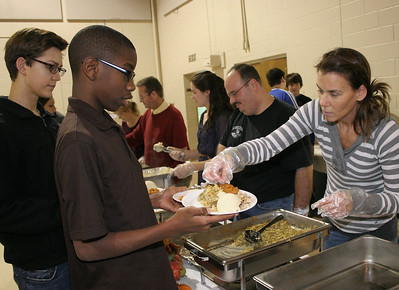 Brandon Swain (foreground) and Jeremy Saxon (left) serve Thanksgiving meals at St. Mary's. Karen Davis is filling Brandon's serving plate. Alongside Karen Davis are Mr. Scarvelli and his daughter Kathryn. photo by Ray Riedel