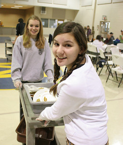 Jamie Krantz (foreground) and Brandi Taylor clear tables at the St. mary's free Thanksgiving meal. photo by Ray Riedel