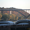 """Smith Avenue High Bridge<br /> MN-149 Mississippi River Crossing<br /> Saint Paul, MN <a href=""""http://www.johnweeks.com/bridges/pages/ms07.html"""">http://www.johnweeks.com/bridges/pages/ms07.html</a><br /> """"... With their bridge now gone, residents of West Saint Paul lobbied hard for a new bridge to restore their access to the West 7th Street area of Saint Paul. The new bridge opened in 1987, and was heralded as one of the seven engineering wonders of Minnesota. It is a magnificent structure towering 160 feet above the river, making it the highest bridge in the city of Saint Paul. The huge steel supports under the bridge looked like a giant letter W, with the two bottom points sitting on piers, and the center forming a large steel arch. To appease the locals who fondly remembered the old High Bridge, MN-DOT incorporated some of the iron salvaged from the old bridge to manufacture the railings for the new bridge.<br /> <br /> As soon as it got cold, the bridge contracted a little more than was planned, and one of the steel sections shifted, causing the center point of the W to no longer meet. Instead, the two beams shifted 11 inches, leaving a huge drop-off on the bridge. The bridge was closed several months while engineers designed a way to move the arches back into position and remove the ski-jump from the roadway. ...""""<br /> <br /> <br /> <br /> Walking St. Paul's High Bridge gives you the sensation of being airborne<br /> Share on printShare on email<br /> By Andy Sturdevant 