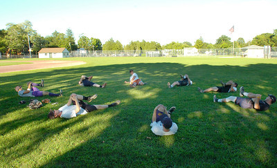 Saratoga 19U players loosen up before a light practice Tuesday evening at West Side Rec Field. Ed Burke 8/7/12