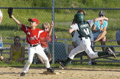 Wilton Rebel first baseman Mason Cox gets the out on Clifton Park runner Kellan Kennedy. Ed Burke 7/27/11