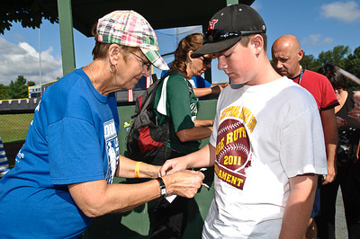 Sean Ryan gets his wristband for the 2011 Babe Ruth World Series Game in Clifton Park from Carol O'Connell Friday Morning. Photo By Eric Jenks 8/26/11