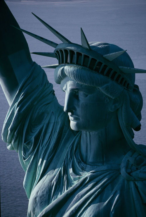 """The Statue of Liberty, standing atop her pedistal in New York harbor. Originally dedicated on 28 October 1886, she is also known as """"Liberty Enlightening the World"""" and is recognized throughout the world as a symbol of American freedom and opportunity."""