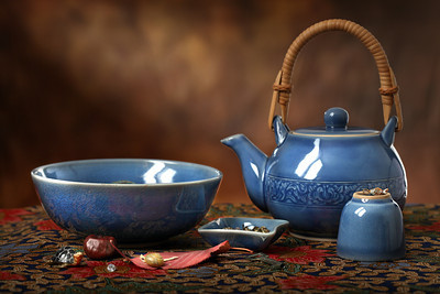 Blue celedon teapot, bowl and cup on a batik cloth with a sunbeam in the background